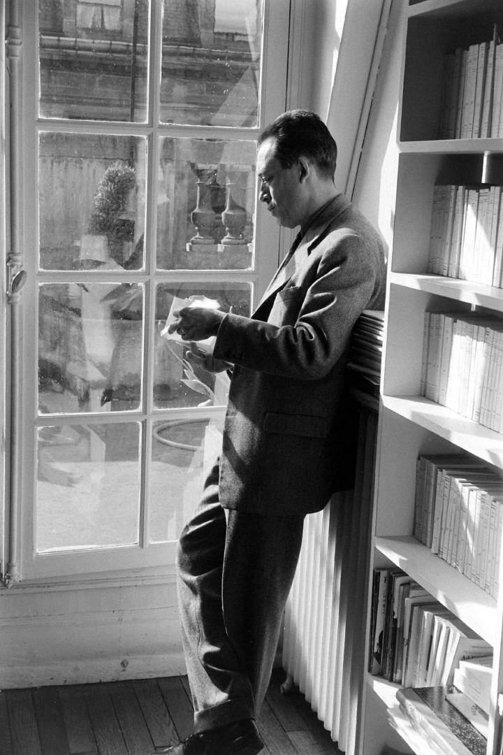 Albert Camus front of the book shelves.
